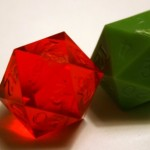 Photograph of two twenty sided dice from GameScience, one opaque green and one translucent red. The 7 face in on top of both, and flashing is visible along one edge of the 7 face.